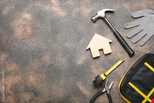 Fototapeta Model of house with supplies on dark background obraz