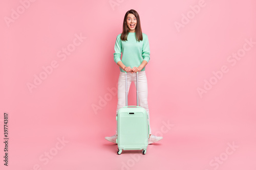 Full length body size view of pretty cheerful girlish girl traveler having fun with valise isolated on pink pastel color background