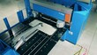 Automated factory machine is cutting an aluminum plate at a factory facility.