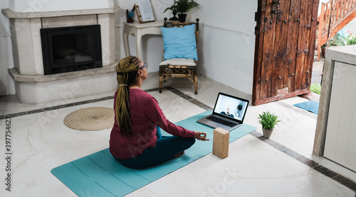 Obraz African senior woman doing online yoga lesson at home during coronavirus outbreak - Old female person meditating using computer laptop - Technology and zen concept - Focus on hand - fototapety do salonu
