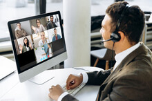 Online Video Conference. Successful Young Adult Businessman Or Manager With Headphones Discuss With Colleagues By Video Call About Financial Graphs And Strategy And Another Working Moments