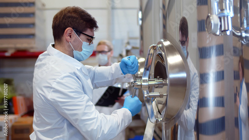 Foto Concentrated experienced brewing technician in coat and mask turning handle of b