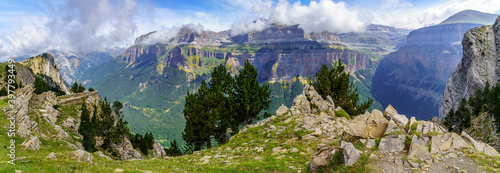 Green landscape in the Pyrenees of the Ordesa and Monte Perdido valley with mountains, rocks, forests and sky with clouds. Top aerial view.