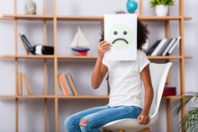 African American Girl With Autism Covering Face With Unhappy Expression On Paper While Sitting On Chair With Blurred Office On Background