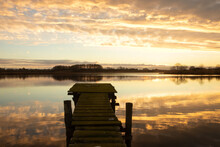 Tranquil Lakeside View With Jetty And Dramatic Evening Sky.