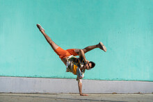 Casual Man Doing Handspring In Front Of Green Wall