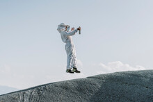 Man Wearing A Beekeeper Dress Jumping On A Hill