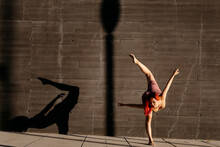 Dancing Young Woman Casting Shade On Black Wall At Sunset