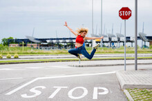 Young Woman Jumping Mid-air In The Street Over Stop Sign