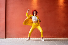 Young Woman In Yellow Suit Wearing Headphones, Dancing To Music From Her Smartphone