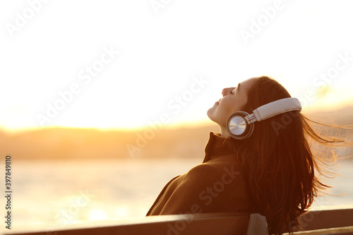 Fotografie, Tablou Woman listening to music breathing on a bench in winter