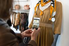 Gros Plan Des Mains D'une Commerçante Photographiant Un Détail D'un Vêtement Pour Femme Sur Le Mannequin De Sa Boutique