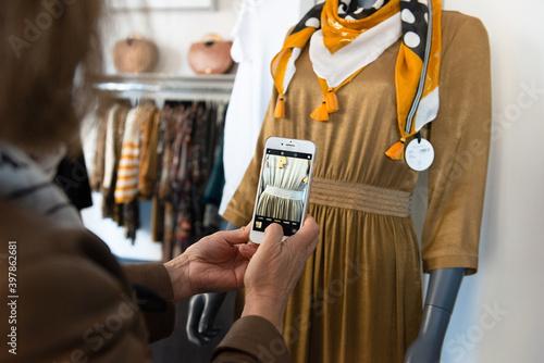 Obraz Gros plan des mains d'une commerçante photographiant un détail d'un vêtement pour femme sur le mannequin de sa boutique - fototapety do salonu