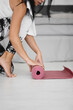 Close up of woman rolling fitness or yoga mat before or after sport practice.