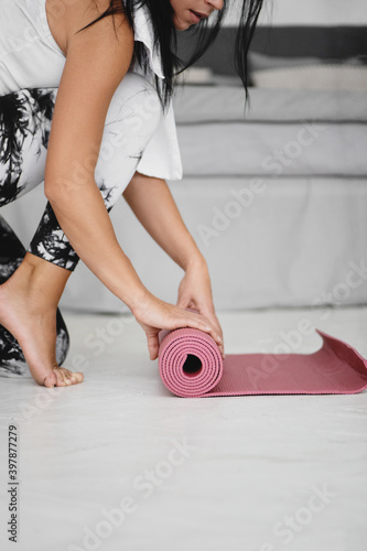 Obraz na plátne Close up of woman rolling fitness or yoga mat before or after sport practice
