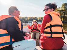 Cheerful Father, Little Son And Teenage Daughter Sitting On Boat In Life Vests On Summer Day. Family Walks At The Boat Station, Selective Focus
