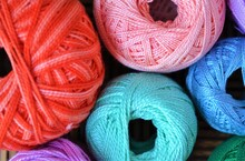 Balls Of Thread Of Different Colors To Crochet On A Wooden Table