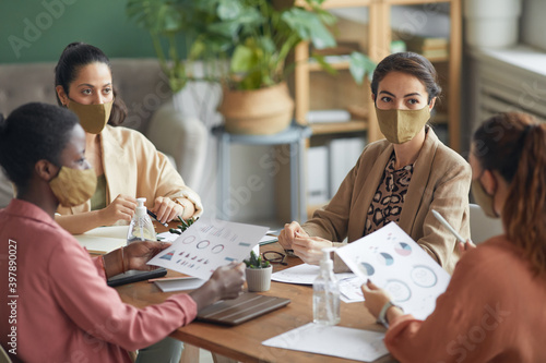 High angle view at multi-ethnic group of young businesswomen wearing masks during meeting in office, copy space