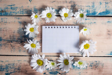 Blank Notebook With White Flower And Bas Ket Of Flower On Vintage Wooden Table