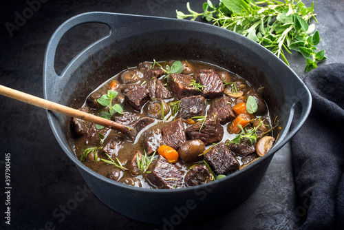 Fototapeta Modern style traditional French boeuf bourguignon with mushrooms and carrots in red wine sauce served as close-up in a Design casserole obraz