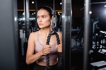 Fototapeta na wymiar athletic sportswoman looking away while exercising on cable pushdown machine on blurred foreground