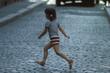 canvas print picture - Kleines Mädchen rennt über Strasse