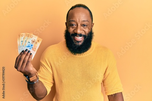 Fototapety, obrazy: Young african american man holding 10 swiss franc banknotes looking positive and happy standing and smiling with a confident smile showing teeth