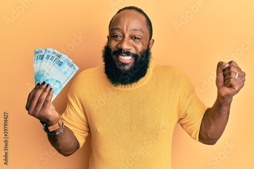 Fototapety, obrazy: Young african american man holding 100 brazilian real banknotes screaming proud, celebrating victory and success very excited with raised arm