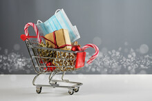 Shopping Cart Model With Gift, Christmas Decoration, Sweets And A Surgical Face Mask Against Coronavirus Infection, Safe Holiday Purchases During The Covid-19 Pandemic, Copy Space