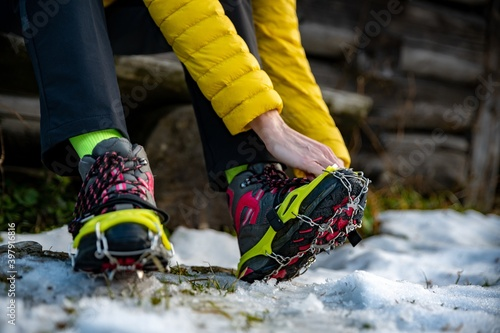 Fototapeta Hands female mountaineers wear crampons for boots before climbing the mountains in winter. obraz