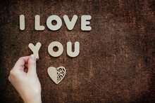 I Love You Concept On Bronze Sackcloth. Female Hand, Wooden Hearts And Letters.