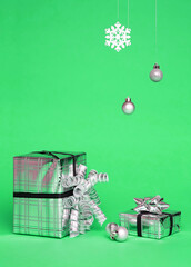 Two silver shiny boxes with a bow - New Year's gift under a Christmas tree with green background