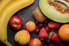 Primer Plano Cenital De  Cerezas Frutillas Banana Kiwi Melon Durazno Damasco Naranja  Sobre Base Gris Oscuro De Cemento Con Textura Con Espacio Para Texto Sin Personas