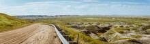 Panorama Shot Of Wrinkled Landscape In Badlands National Park With Road After Sunrise In America