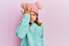 Little Beautiful Girl Wearing Wool Sweater And Cute Winter Hat Surprised With Hand On Head For Mistake, Remember Error. Forgot, Bad Memory Concept.
