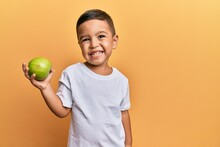 Adorable Latin Toddler Smiling Happy Holding Green Apple Looking To The Camera Over Isolated Yellow Background.