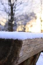 朝日が昇る時、木のテーブルに積もった雪