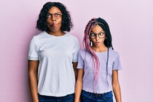 Beautiful African American Mother And Daughter Wearing Casual Clothes And Glasses Making Fish Face With Lips, Crazy And Comical Gesture. Funny Expression.