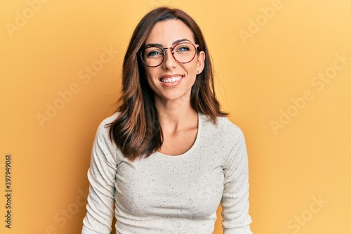 Young brunette woman wearing casual clothes and glasses with a happy and cool smile on face. lucky person.