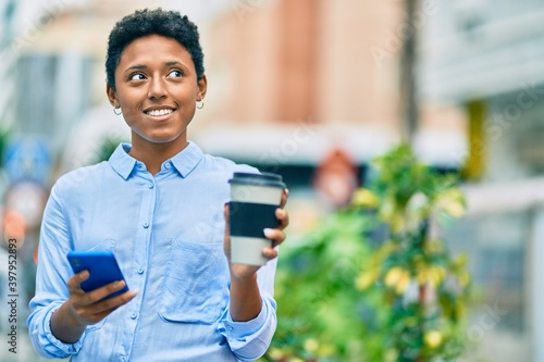 Fototapety, obrazy: Young african american girl using smartphone and drinking take away coffee at the city.