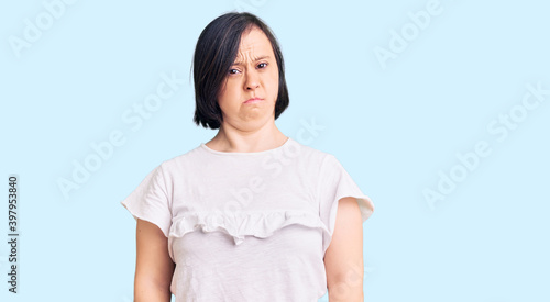 Fotografie, Obraz Brunette woman with down syndrome wearing casual white tshirt skeptic and nervous, frowning upset because of problem