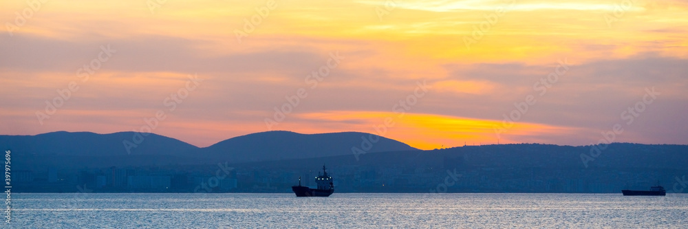 Fototapeta Golden sunset, silhouette of the city and cargo ship. Beautiful architecort by the sea on the background of the sunset