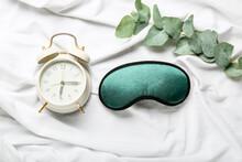 Sleep Mask And Alarm Clock On Light Background