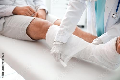 Foto Doctor putting broken leg of young man in plaster