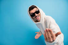 Photo Portrait Of Cool Guy In Black Glasses Telling You To Come Here Showing Blank Space Wearing Wool Hoodie Isolated On Pastel Blue Colored Background