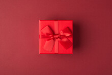 Flat Lay Layout Close Up View Photo Of Small Present Box With Bow And Ribbon Isolated Maroon Color Background