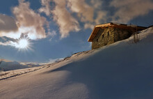 Traditional French Alpine Chalet At The Top Of Snowy Mountain At Sunset