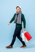 Handsosme Asian Man In Christmas Theme Attrie Walking And Holding Shopping Bags In Light Blue Studio Backgground