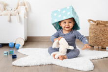 Happy Baby In Playroom With Basket On Head