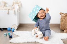 Smiling Baby In Playroom With Basket On Head